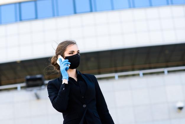 Bella imprenditrice in un abito nero in una maschera medica nera e guanti in città in quarantena e isolamento. pandemia covid-19. messa a fuoco selettiva