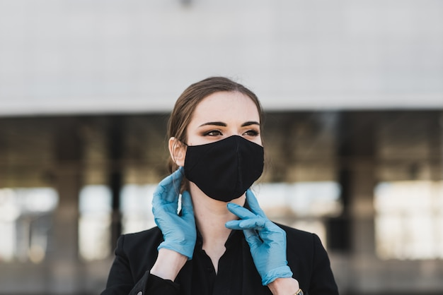 Bella donna d'affari in un abito nero in una maschera medica nera e guanti in città in quarantena e isolamento. pandemic covid-19. messa a fuoco selettiva