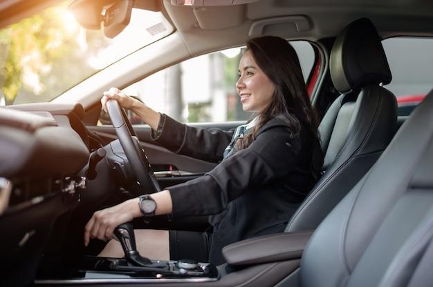 Bella imprenditrice alla guida di auto al tramonto