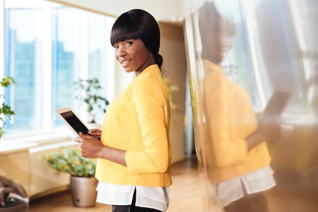 Bella donna di affari che tiene il computer tablet in ufficio e guarda davanti