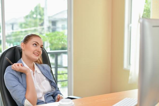 La bella donna di affari sta lavorando in ufficio