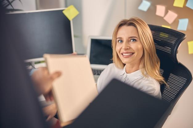 Bella donna d'affari che guarda il collega e sorride mentre gli porge i documenti in ufficio
