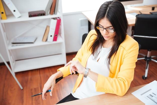 Bella donna d'affari che guarda l'orologio da polso in ufficio
