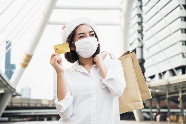 Bella imprenditrice shopping con carta di credito in un centro commerciale nel cuore del paesaggio urbano