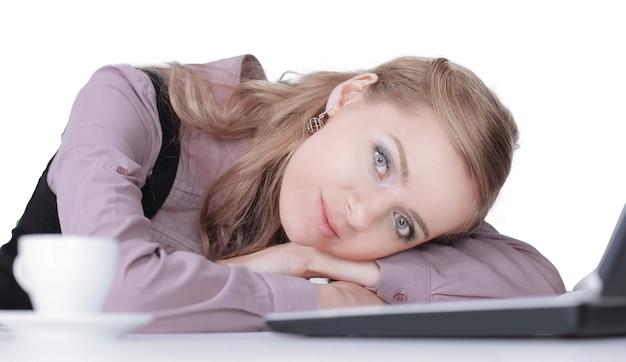 Bella donna di affari che dorme sulla tastiera del computer portatile dopo il lavoro.