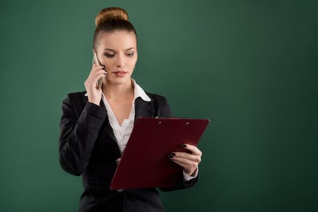 Bella imprenditrice parlando al telefono cellulare durante la lettura negli appunti