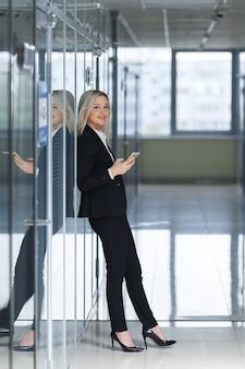 Bella donna di affari che utilizza smartphone in ufficio.