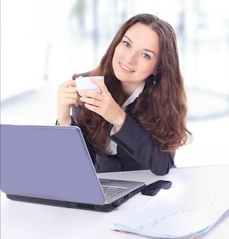 Bella donna d'affari con una tazza di caffè in ufficio.