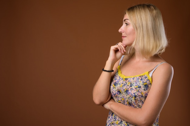 Bella donna di affari con capelli biondi corti contro il dorso marrone