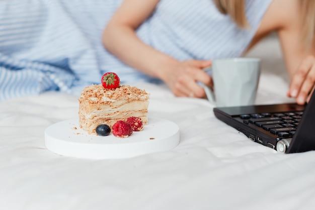 Primo piano bello della torta sul letto accanto a una colazione di lavoro del computer portatile