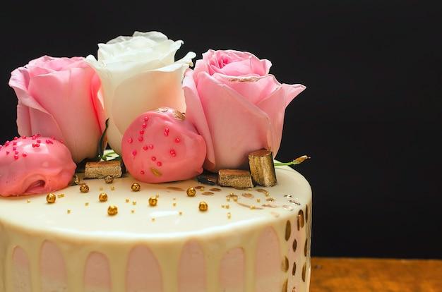 Bella torta decorata con rose naturali e cioccolatini su un tavolo di legno fatto in casa