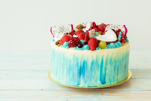 Bella torta con frutti di bosco e frutta su un tavolo di legno