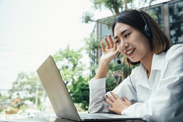 Bellissimo personale del call center che parla e fornisce servizi ai clienti tramite cuffie e cavo del microfono all'esterno del paesaggio urbano professionisti con capacità di registrazione delle informazioni e del servizio vocale