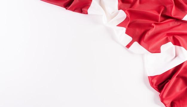 Una bella bandiera nazionale del canada tessuto in tessuto un segno o un simbolo del concetto di giorno del canada su sfondo bianco