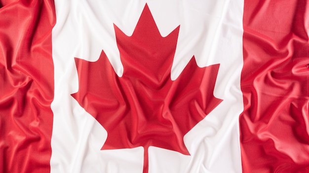 Un bellissimo tessuto della bandiera nazionale del canada un segno o un simbolo del concetto di giorno del canada