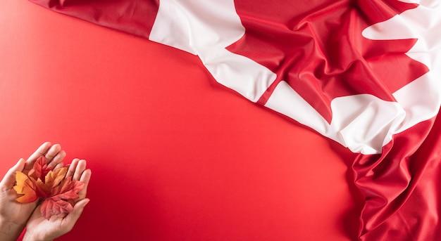 Un bellissimo tessuto della bandiera nazionale del canada con la mano che tiene la foglia d'acero su sfondo rosso un segno o un simbolo del concetto del giorno del canada