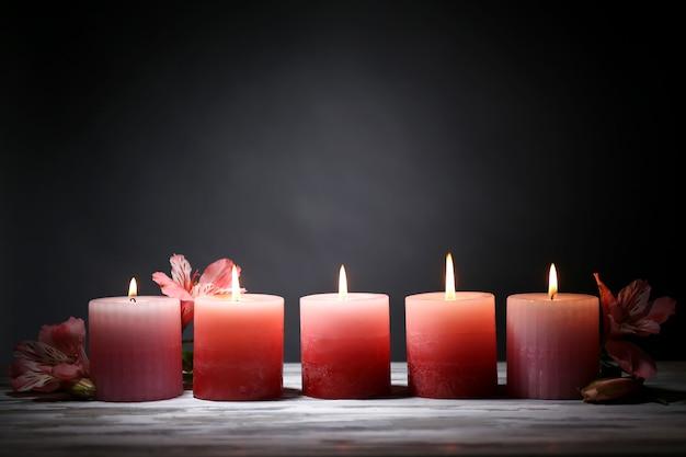 Belle candele con fiori sulla tavola di legno, su oscurità