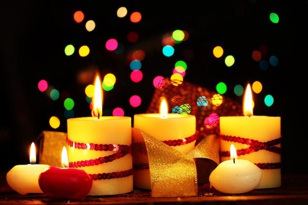 Belle candele sul tavolo di legno su sfondo luminoso