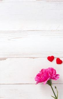 Bellissimi garofani e cuori forma con bianco scheda vuota isolata su un luminoso tavolo in legno, copia spazio, laici, vista dall'alto, mock up