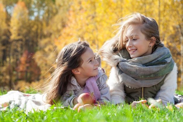 Le belle sorelle grandi e piccole caucasiche si trovano sul plaid, giocano con le mele rosse su fondo di erba verde degli alberi dorati della foresta di autunno. weekend in famiglia concetto all'aperto, persone, stile di vita