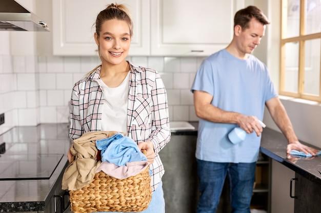 Belle coppie caucasiche trascorrono i fine settimana insieme a pulire casa, donna che tiene cesto con stracci sporchi e cose mentre il marito aiuta la moglie usando detersivi