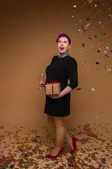 Bella femmina caucasica in abito nero tiene un bicchiere di vino rosa e un regalo, foto isolato sulla parete marrone