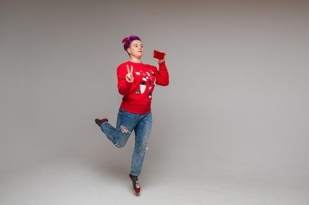 Bella femmina caucasica in accogliente maglione rosso con stampa natalizia prende le foto sul suo telefono, immagine isolata sul muro bianco