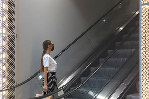 Bella ragazza caucasica in una maschera protettiva nera in un centro commerciale con borse della spesa sulla scala mobile nuovo normale