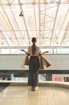 Bella ragazza caucasica in una maschera protettiva nera in un centro commerciale con borse della spesa in piedi con le spalle alla telecamera nuovo normale