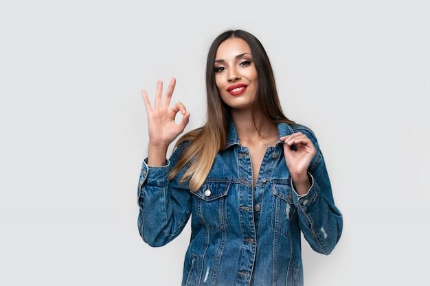 Giacca di jeans bella ragazza caucasica in posa in studio su sfondo bianco brunetta carina denim moda labbra rosse compongono giovane donna adulta in piedi all'interno sorpreso ammirato mostra ok segno gesto