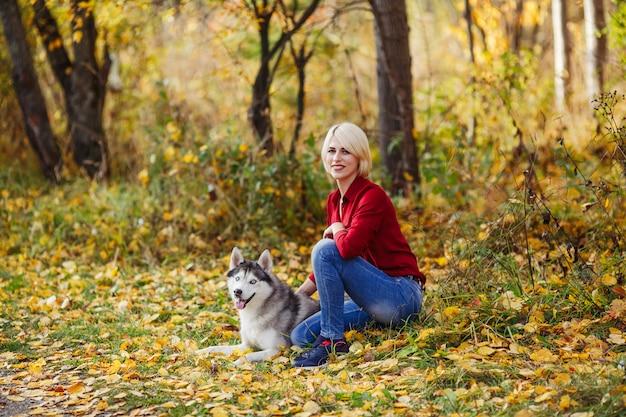 La bella ragazza caucasica gioca con il cane husky nella foresta di autunno