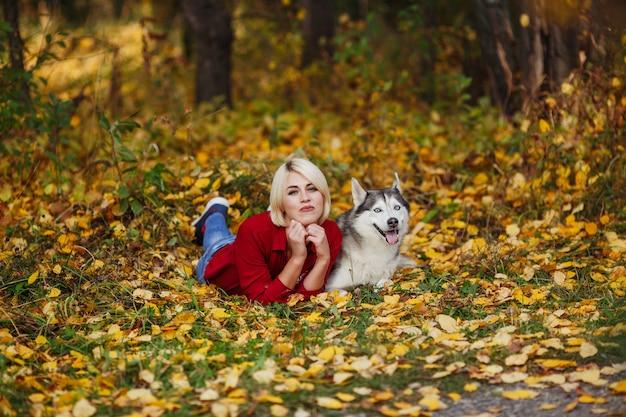 Bella ragazza caucasica gioca con il cane husky nella foresta di autunno