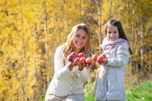 Bella madre caucasica, la piccola figlia gioca con le mele rosse mature su fondo di erba verde degli alberi dorati della foresta di autunno. weekend in famiglia concetto all'aperto, persone, tempo, stile di vita