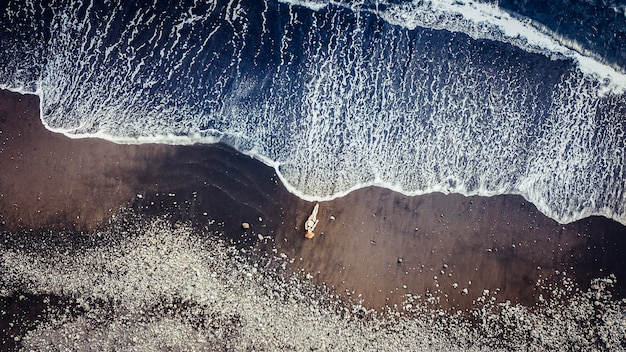 Bello modello caucasico della gente sulla spiaggia sabbiosa a tenerife che prende il sole mentre una grande onda viene da lei. concetto aereo di vacanza con drone. meditazione e gioiosa per uno stile di vita indipendente
