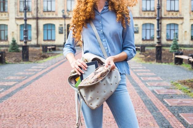 Una bellissima ragazza dai capelli rossi caucasica tira fuori dal suo zaino un tablet e-book