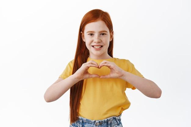 Bella bambina rossa caucasica, bambino con i capelli rossi e le lentiggini mostra ti amo, segno di cuore e sorrisi adorabili davanti, muro bianco