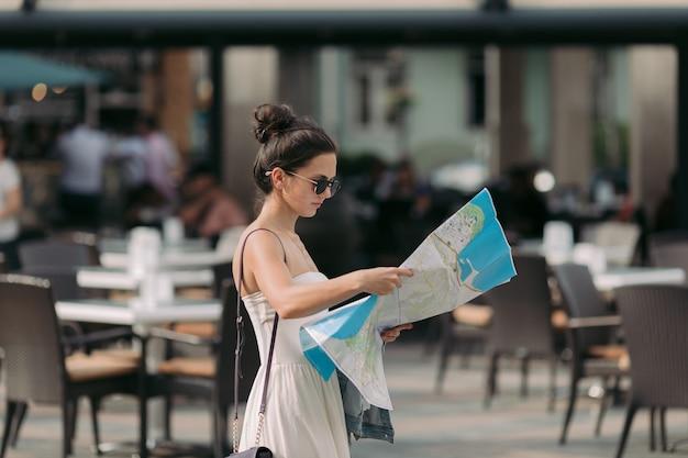 Bella donna turistica caucasica guardando la mappa sulla strada della città