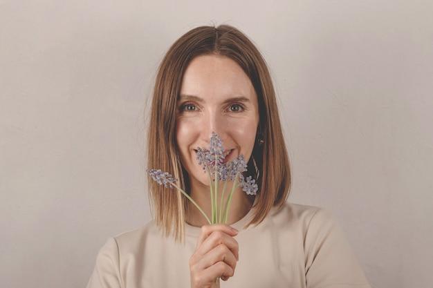 Bella donna caucasica che tiene i fiori muscari nelle sue mani