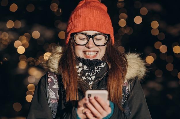 Bella donna caucasica che utilizza la tenuta della mano dello smart phone all'aperto nella notte della città, sorridendo, schermo illuminato faccia illuminata