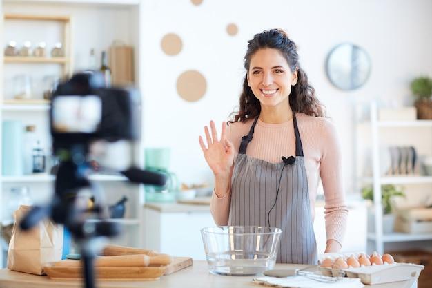Grembiule da portare della bella donna caucasica che inizia il suo video del blog dell'alimento con il saluto dei suoi spettatori