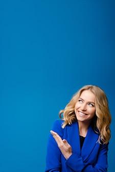 Alla bella donna caucasica con i capelli ondulati chiari in una giacca blu piace isolato su sfondo blu
