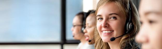 Bella donna caucasica che lavora in call center con colleghi internazionali