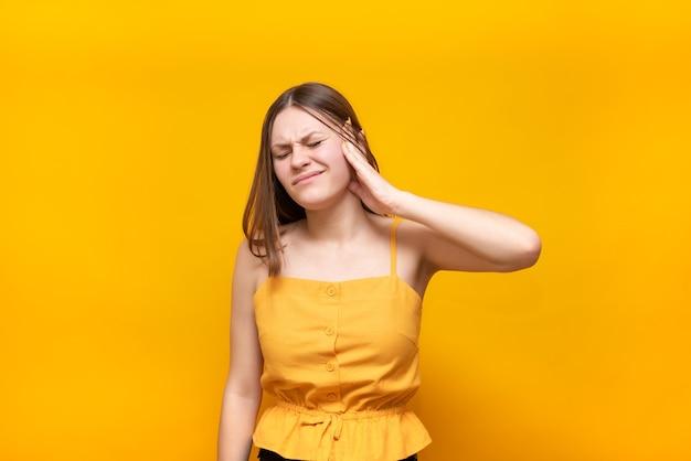 La bella donna caucasica in un maglione giallo tiene il suo orecchio su un giallo