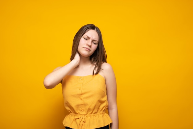 Una bella donna caucasica in un maglione giallo tiene il collo su un giallo