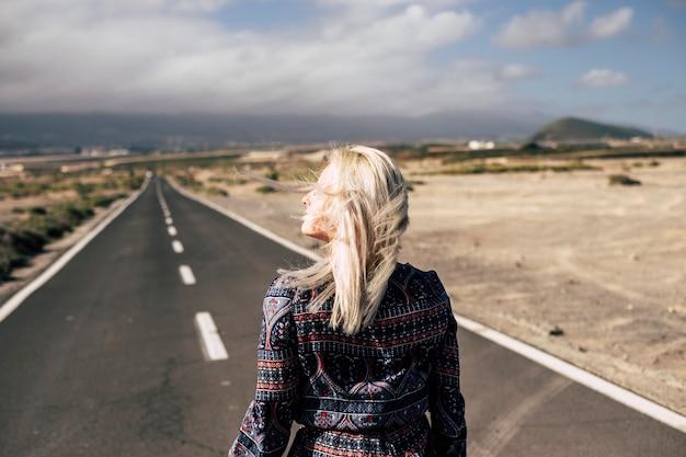 Bella ragazza bionda caucasica che cammina su una lunga strada ed esplora e scopre il mondo. concetto di viaggio e live per viaggiatore solitario in voglia di viaggiare. giornata estiva ventosa