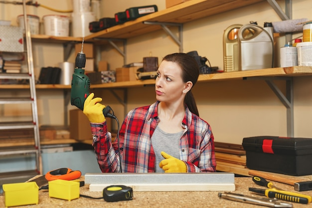 Bella giovane donna caucasica dai capelli castani in camicia a quadri e maglietta grigia che lavora in un laboratorio di falegnameria al posto del tavolo, perforando con fori in un pezzo di ferro e legno mentre si realizzano mobili.
