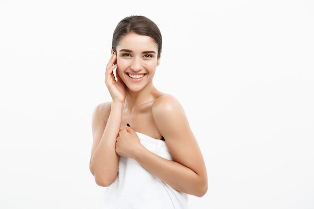 Asciugamano d'uso della bella giovane donna caucasica dopo la doccia