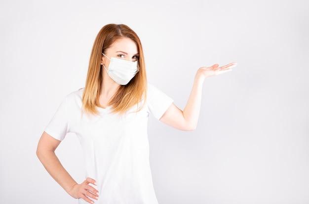 Bella giovane donna caucasica in maglietta bianca con maschera usa e getta. protezione contro virus e infezioni.