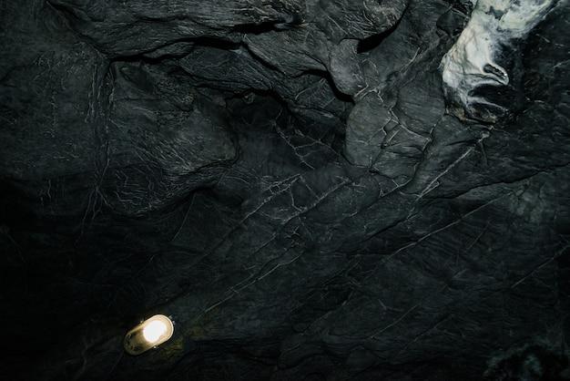 Bella grotta. vista dall'interno della prigione buia. pareti strutturate della grotta. immagine di sfondo del tunnel sotterraneo. umidità all'interno della grotta. illuminazione all'interno della grotta per escursioni.