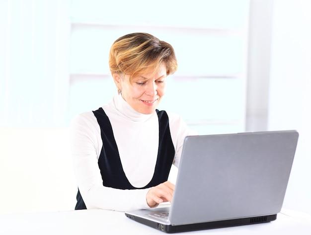Bella e affascinante donna d'affari per un laptop.